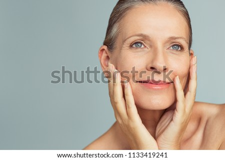 Portrait of mature woman with perfect skin isolated on grey background. Closeup face of happy senior woman with hands on cheeks looking away. Facing aging with a carefree attitude. #1133419241