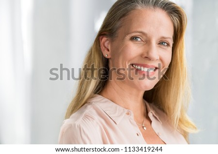 Portrait of mature woman enjoying life after retirement and looking at camera. Closeup face of happy senior woman with blond hair smiling. Beautiful smiling lady indoor. #1133419244