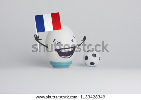 france football. funny and funny football player. emotional fan. on a white background. an egg with a flag holding a flag in his hand #1133428349