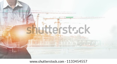 Engineer standing using tablet control and manage work at construction site.