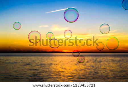 Soap bubbles on sunset water horizon background. Sunset soap bubbles water view. Sunset water soap bubbles #1133455721