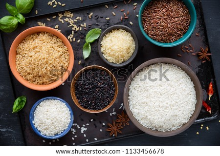 Variety of types and colours of rice - red, black, basmati, whole grain, long grain parboiled and arborio - in bowls. Overhead view #1133456678