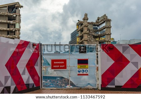 Entrance gate to construction site with demolition work in background. Royalty-Free Stock Photo #1133467592