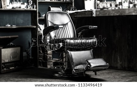 Barber shop chair. Stylish vintage barber chair. Barbershop armchair, modern hairdresser and hair salon, barber shop for men. Barbershop theme. Hairstylist in barber shop interior. Black and white. #1133496419