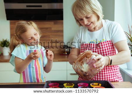 Portrait of happy beautiful grandmother and her granddaughter in modern kitchen #1133570792