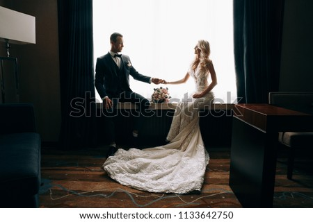 Wedding photo shooting.Married couple embracing and looking at each other.Holding bouquet.Sensual photo of the groom and bride.Bride and groom, couple in love during a wedding photo session #1133642750