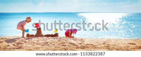 Boy and girl playing on the beach on summer holidays. Children building a sandcastle at sea #1133822387