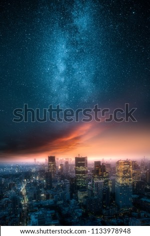 Dramatic view of a city skyline at night with red clouds painted by setting sun and beautiful milky way up on the sky
