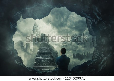 Surreal view as a man escape from a dark cave stand in front of a mystic stairway crossing the misty abyss going up to unknown paradise. Opportunity staircase, exit way to success, freedom concept. #1134009971