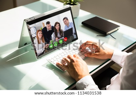 Businessman's hand video conferencing with his colleagues on laptop #1134031538