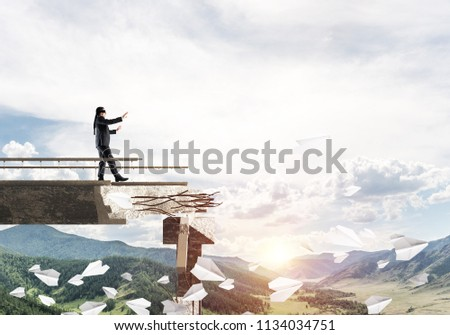 Businessman walking blindfolded on concrete bridge with huge gap as symbol of hidden threats and risks. Skyscape and nature view on background. 3D rendering. #1134034751