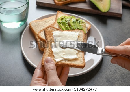 Woman spreading butter on toasted bread at table, closeup Royalty-Free Stock Photo #1134272477