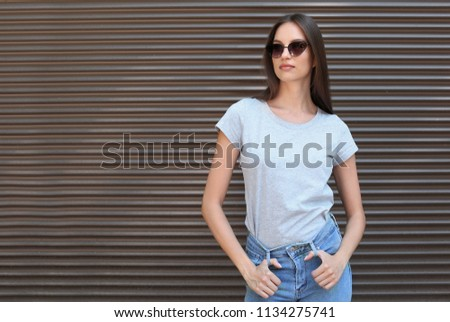 Young woman wearing gray t-shirt near wall on street. Urban style #1134275741