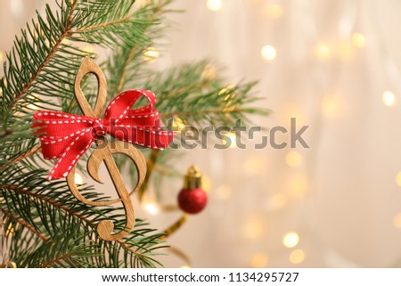 Fir tree branch with wooden treble clef on blurred background. Christmas music concept #1134295727