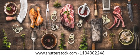 Flat lay of various grill and bbq meat : chicken legs, steaks, lamb ribs with vintage kitchenware kitchen utensils:  Meat Fork and Butcher Cleaver and herbs knife. Sauces and ingredients for grilling, #1134302246
