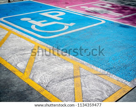 Disabled handicap parking space reserved for handicapped, white handicapped icon on blue background and lady comfortable parking area in pink background.