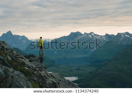 Traveler man standing on the edge cliff over clouds sunset mountains travel adventure lifestyle journey vacations in Norway #1134374240