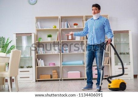 Injured man with neck injury vacuum cleaning house #1134406091