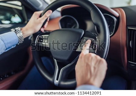 close up of male hands pushing button on the steering wheel in the car #1134412091