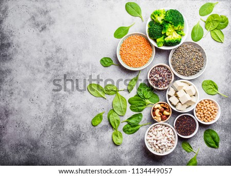 Top view of different vegan protein sources with space for text: beans, lentils, quinoa, tofu, vegetables, nuts, chickpeas, rice, stone background. Healthy balanced vegetarian nutrition for vegans  #1134449057