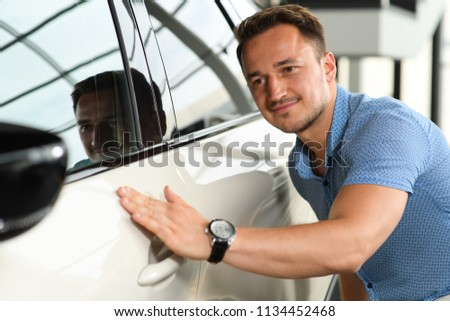 Men in blue t-shirt touching new car. He want to buy new car. Car is white. #1134452468
