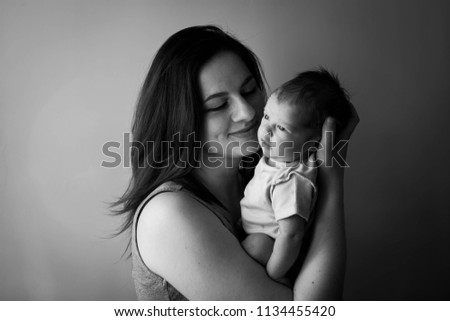 contrast black and white photo, young mother holding a newborn baby boy, soft focus #1134455420