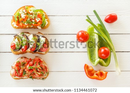Bruschetta with fresh tomatoes and cheese, eggplant and mozzarella, sweet pepper and goat cheese on white boards with fresh vegetables. Top view. Copy space. #1134461072