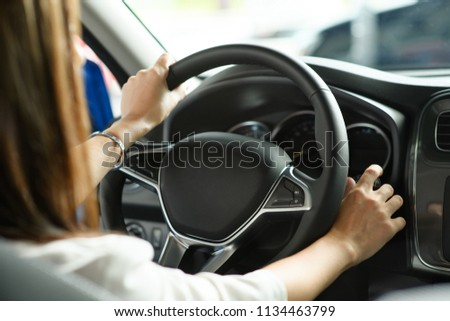 Woman hands hold wheel in new car, she is trying to feel the car #1134463799