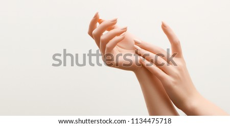 Beautiful Woman Hands. Female Hands Applying Cream, Lotion. Spa and Manicure concept. Female hands with french manicure. Soft skin, skincare concept. Hand Skin Care. Royalty-Free Stock Photo #1134475718