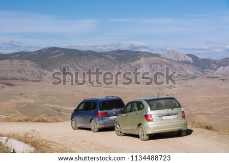 Volkswagen Sharan and Honda FR-V. The car is parked on a mountain Meganom near wind turbines. Republic of Crimea. October 30, 2015. #1134488723