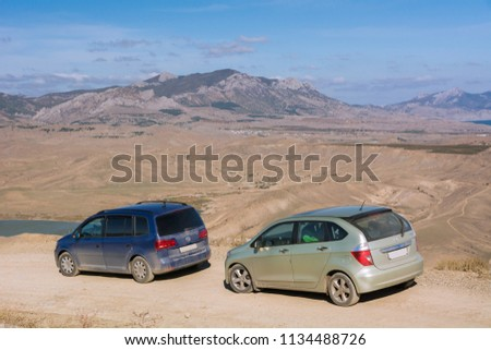 Volkswagen Sharan and Honda FR-V. The car is parked on a mountain Meganom near wind turbines. Republic of Crimea. October 30, 2015. #1134488726