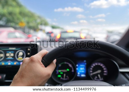 Man hands driver on steering wheel of a modern car with Car dashboard and beautiful sky background.Traffic jam on rush hour in the city.Transport,Vacation,Holiday,Travel and Automobile Concept. #1134499976