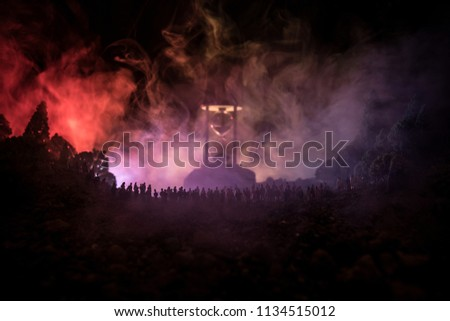 Silhouette of a large crowd of people in forest at night standing against a big hourglass with toned light beams on foggy background. Time concept. Hourglass measuring the passing time #1134515012