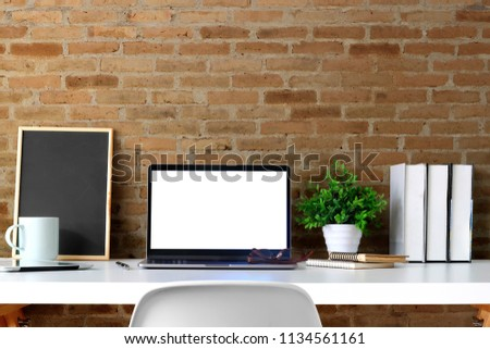 Front view mockup laptop with poster on white table and red brick wall. Blank screen laptop and poster frame for graphic display montage. #1134561161