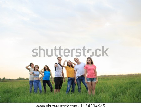 Young people against the beautiful sunset sky, Group of young people on the field #1134594665