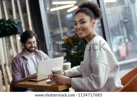 Young people man and woman coworking together at creative stylish office sitting at the table girl turn to camera drinking hot coffee smiling cheerful while guy working on laptop #1134717683