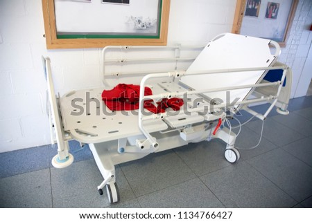 stripped hospital bed in corridor with red band on it under picture frame on wall