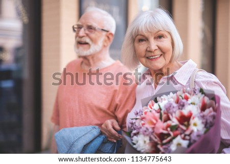 Waist up portrait of smiling senior lady strolling with male outside. She is happily holding bunch of flowers and looking at camera with joy #1134775643