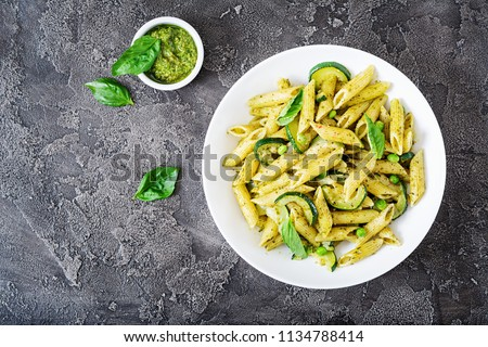 Penne pasta with  pesto sauce, zucchini, green peas and basil. Italian food. Top view. Flat lay. #1134788414