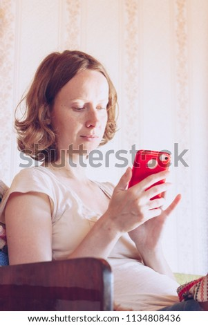 young girl is using smartphone while sitting on couch. #1134808436