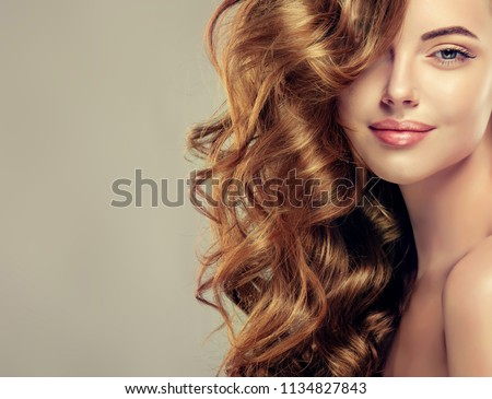 Brunette  girl with long  and   shiny curly hair .  Beautiful  model woman  with wavy hairstyle   .Care, cosmetics and beauty  #1134827843