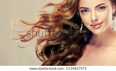 Brunette  girl with long  and   shiny curly hair .  Beautiful  model woman  with wavy hairstyle   .Care, cosmetics and beauty  #1134827975