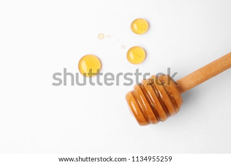 Drops of honey and dipper on white background, top view #1134955259