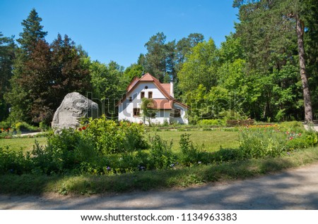 RUSSIA, TULA REDION - JUNE 18, 2018: Museum-Reserve of Vasily Dmitrievich Polenov. Memorial stone and small house of European style. #1134963383