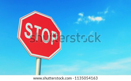 Red road stop sign on a blue sky background