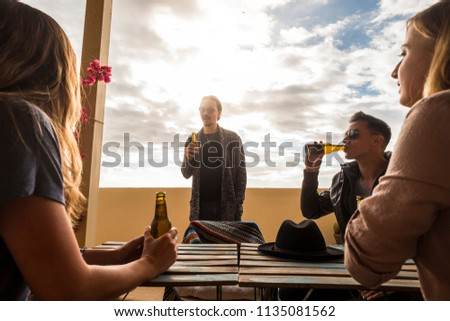 group of young caucasian people stay together in the rooftop terrace speaking and drinking beers. leisure activity for nice men and women. trendy and nice lifestyle. sky in the background #1135081562