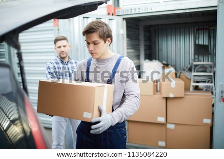 Serious young male mover carrying cardboard box from large container with stacking stuff while loading car for client outdoors #1135084220