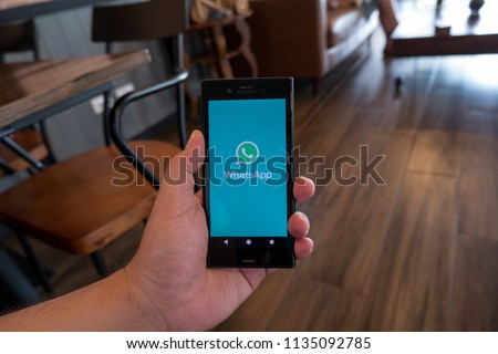 a man holding mobile with social network screen in cafe #1135092785