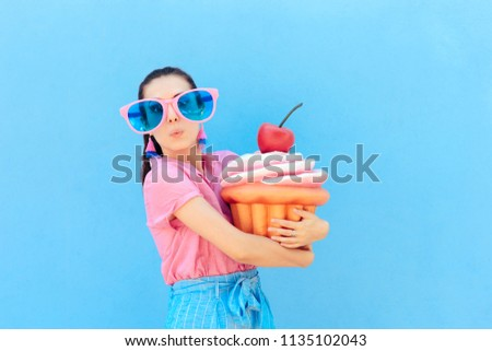 Funny Party Girl with Big Sunglasses and Huge Cupcake. Cute woman wearing silly glasses holding huge cake  #1135102043
