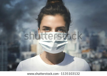 Air pollution in the city. Woman wearing face mask for protection. Royalty-Free Stock Photo #1135103132